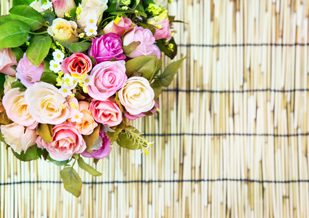 close up of beautiful artificial multicolor roses flowers bouquet decorated on bamboo mat texture use as copy space,background ,backdrop photo