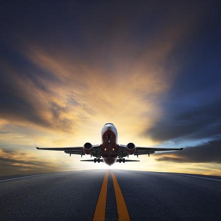航空輸送、旅行、旅行業界のビジネスのためのコピー スペース使用を美しい夕暮れの空に対して滑走路から旅客機が離陸します。 写真素材