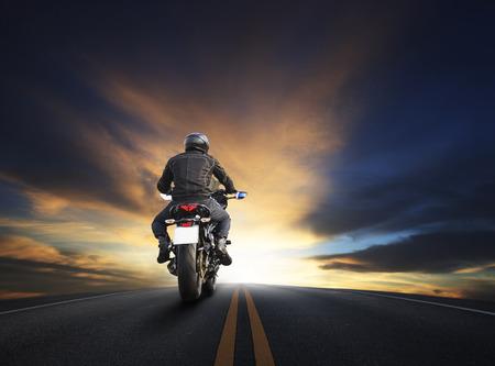 homem novo que monta a grande moto bicicleta no asfalto high way contra bela utilização céu obscuro para o motociclista viajando e tema viagem