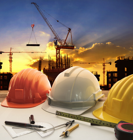 engineer working table plan, home model and writing tool equipment against building construction crane with evening dusky sky  photo
