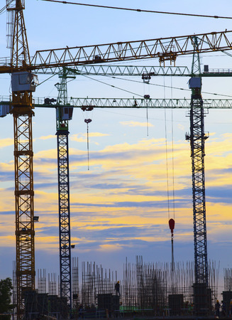 contruction: crane of building construction against beautiful dusky sky use for construction industry business and land development