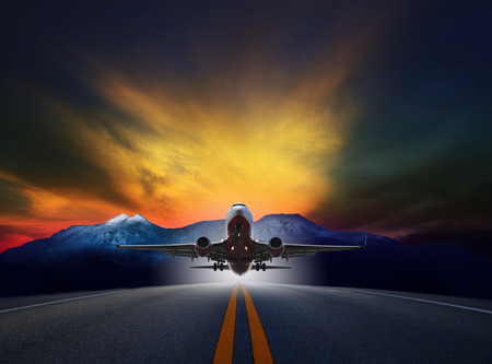 runways: jet plane flying over runways against rock mountain and beautiful dusky sky with copy space use for air transport ,journey and traveling industry business