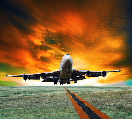 runways: jet plane flying over runways and beautiful dusky sky with copy space use for air transport ,journey and traveling industry business  Stock Photo