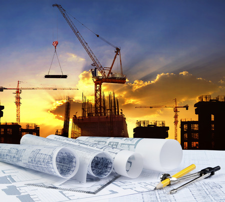building plans: engineer working table plan, home model and writing tool equipment against building construction crane with evening dusky sky  Stock Photo