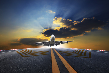 runways: big passenger plane flying over airport runway against beautiful dusky sky use for air transport and traveling business