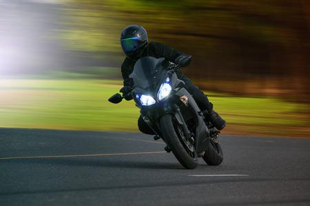 motor race: jonge man rijden op grote fiets motorfiets over asfalt snelweg tegen mooie onscherpe achtergrond te gebruiken voor biker reizen en reis thema