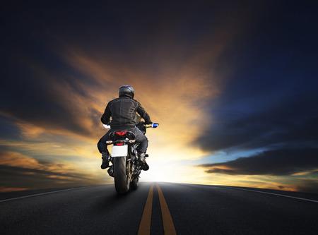 ビッグバイクです。 アスファルト高の方法に乗ってバイクの旅行との旅のテーマの美しい夕暮れの空使用に対して若い男