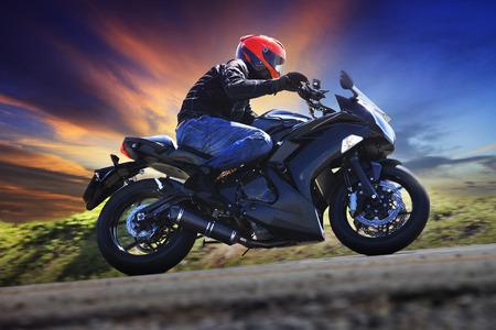 若い男のスポーツ活動、男性レジャー、旅のテーマの夕暮れの空の使用に対してアスファルト田舎道のカーブにオートバイに乗って 写真素材