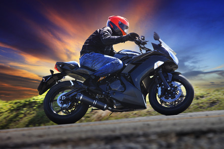 the motor: young man riding motorcycle on curve of asphalt country road against dusky sky use for sport activities,male leisure and journey theme