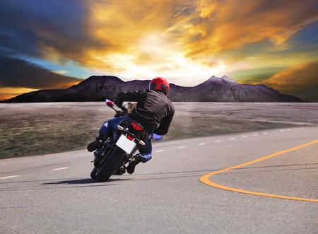 若い男田舎でアスファルト道路曲線と山のシーンのバック グラウンドでバイクに乗っての背面図