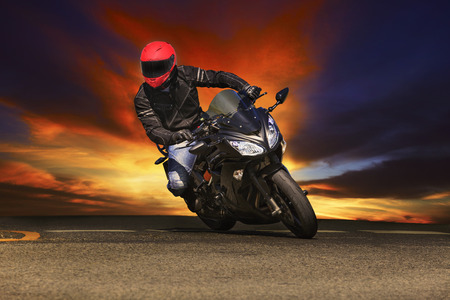 young man riding big bike motorcycle on asphalt roads against beautiful dusky sky use for sport leisure and male activities theme