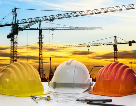drawing instrument: safety helmet and engineering plan with drawing instrument on engineer working table against crane construction and beautiful sun set scene use for construction and land development topic