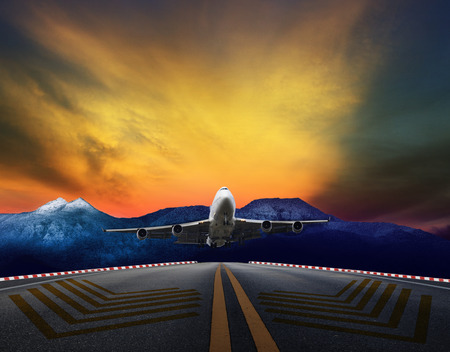 runways: passenger jet plane flying over airport runways against beautiful dusky sky