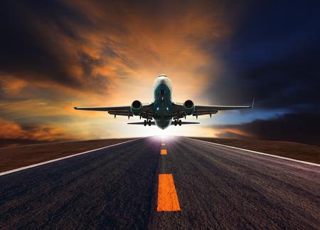ジェット旅客機航空機輸送と貨物物流と旅行業界のための美しい夕暮れの空の使用に対して空港の滑走路の上を飛んで