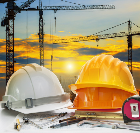 engineering tools: civil engineer working table with safety helmet and writing instrument against beautiful dusky sky and crane construction site