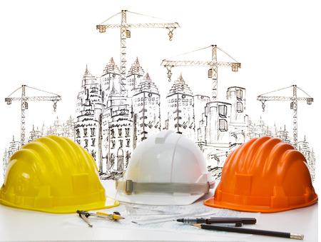 capacete de segurança em engenheiro mesa trabalhando contra esboço de construção civil e de alta guindaste Imagens