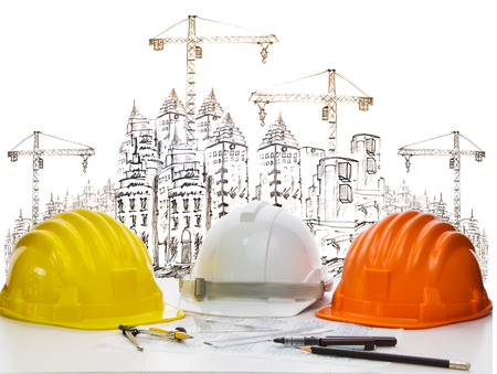 safety helmet on engineer working table against sketching of building construction and high crane  photo