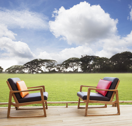 arm chair: relax chairs on wood terrace with grass field and beautiful sky use as natural  Stock Photo