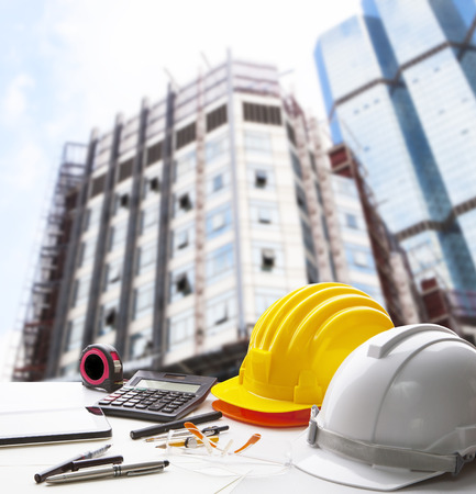 safety helmet and writing instrument on engineering working table against exterior construction building Stock Photo