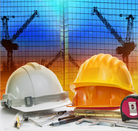 writing instrument: civil engineer working table with safety helmet and writing instrument against beautiful dusky sky and crane construction site
