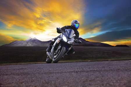 casco de moto: hombre joven que monta la motocicleta en la curva de la carretera de asfalto con el fondo rural y de monta�a