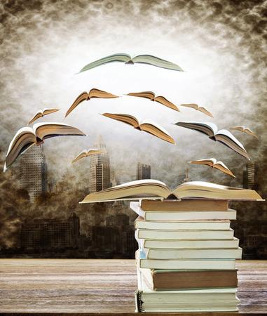 resumen del libro abierto en la pila de libros y volar a la luz por el uso escena urbana para la idea, creativa y tema de educación Foto de archivo