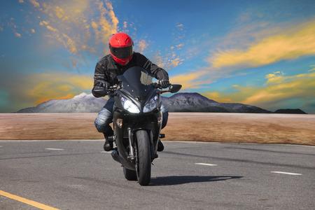 casco moto: hombre joven que monta la motocicleta en el asfalto utilización curva de la carretera para el deporte extremo de ocio