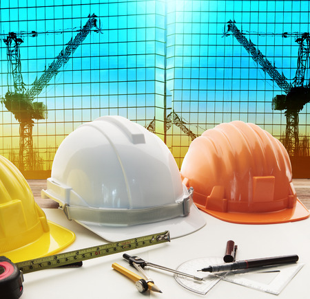 safety helmet on architect ,engineer working table with modern building and crane construction background use for construction business and civil engineering ,real estate topic Stock Photo