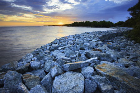 river scape: sun set with rock dam sea coast bank protection perspective line