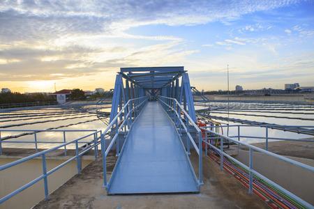 aguas residuales: perspectiva del puente de metal para trabajos en gran tanque de suministro de agua en el agua metropolitana trabaja sitio de la planta de la industria