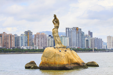 perls:  Zhuhai Fisher Girl sculpture important landmark of visitor when visited to  zhuhai city china against residence building background