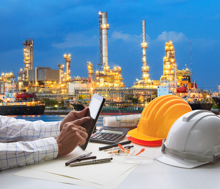heavy industry: engineering working on computer tablet  against beautiful oil refinery background