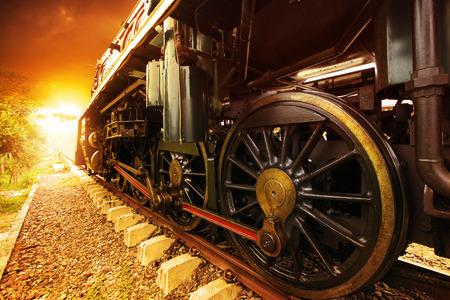 ijzeren wielen van stroom motor locomotief de trein op het spoor te volgen perspectief gouden licht naar voren worden gebruikt voor oude en klassieke vervoer periode land en retro vintage stijl achtergrond