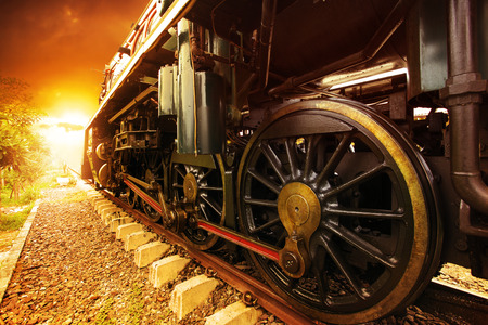 iron wheels of stream engine locomotive train on railways track perspective to golden light forward use for old and classic period land transport and retro vintage style background photo