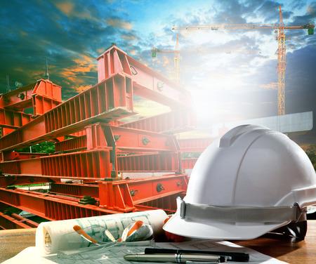 クレーン、道路の建設ツールに対してエンジニア作業テーブルの上の安全ヘルメットのインフラ構造建設産業のテーマを使用します。 写真素材