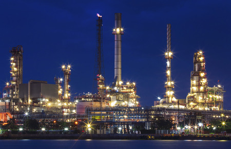 lighting of oil refinery plant in heavy industry estate against beautiful dusky sky use for petrochemical industrial and fuel energy business