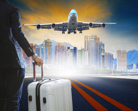 business man and luggage standing on airport runways with passenger jet plane flying above airport runway use for aircraft transport ,traveling ,journey trip with airline