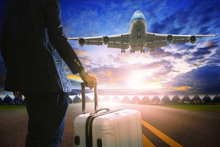 ビジネスの男性と荷物を空港で旅客ジェット飛行機飛行航空輸送と航空会社トピックによって旅行のための美しい空の使用に対して滑走路に立って