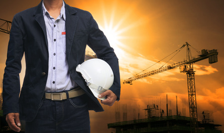 crane parts: engineer man standing with white safety helmet against beautiful dusky sky with building construction site use for engineering and construction industrial business