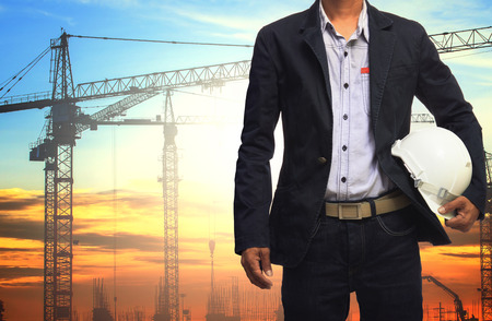 land management: engineer man working with white safety helmet against crane and  building construction site use for civil engineering and construction industrial business Stock Photo