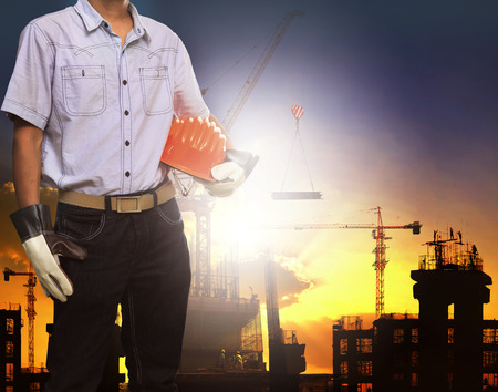 civil engineering: engineer man working with white safety helmet against crane and  building construction site use for civil engineering and construction industrial business Stock Photo