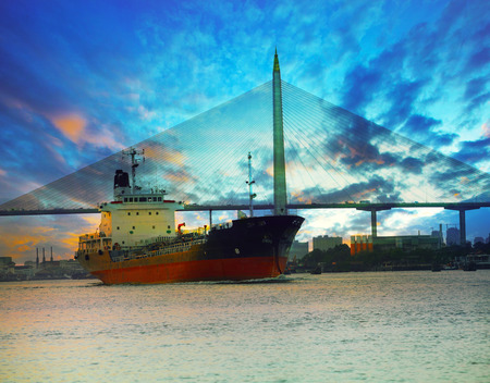 marine industry: tanker ship in river against beautiful bridge with twilight sky of urban scene use for marine transport and freight industry business Stock Photo