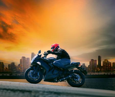 Jonge man en veiligheid pak paardrijden grote motorfiets tegen de mooie donkere hemel en urban scene met een kopie ruimte Stockfoto - 31997587