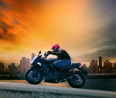 young man and safety suit riding big motorcycle against beautiful dusky sky and urban scene with copy space