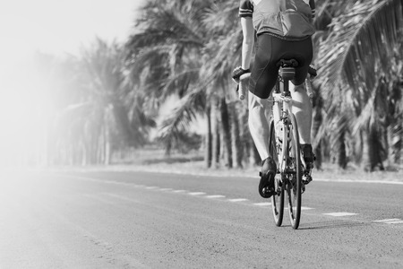 usse: young man riding road biking bycycle on asphalt track in black and white motion usse for sport activities and people outdoor activity