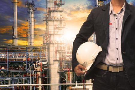 petrochemie industrie: techniek man met witte veiligheidshelm staan voor olieraffinaderij bouwwerk in de zware petrochemische industrie