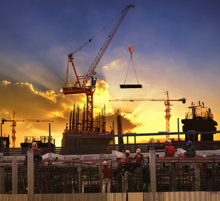 engineering tools: worker working in high building construction site against beautiful dusky sky use for construction business and land ,real estate ,civil development Stock Photo