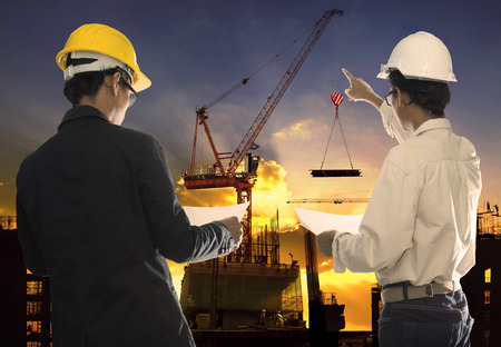 two civil engineer working in building construction site against beautiful dusky sky with crane construction