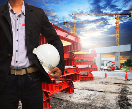 property management: engineer man with safety helmet working in road and bridge construction site