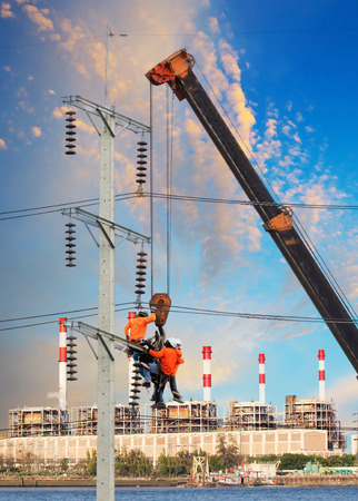 infra construction: electrician worker working on high voltage electric pole with crane against factory building background Stock Photo